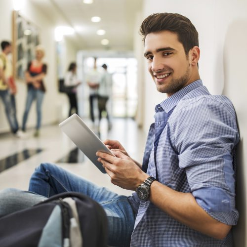 Happy university male student sitting in the school lobby and using digital tablet while looking at camera. There are people in the background.